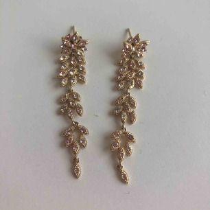 Fina Lily and Rose örhängen i guld med stenar i ljusrosa, ljusblå och silver. Endast använda vid ett tillfälle.