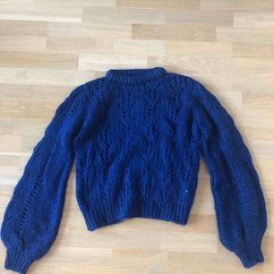 Snygg mörkblå stickad tröja med ballongarmar från Chiquelle. Fint skick