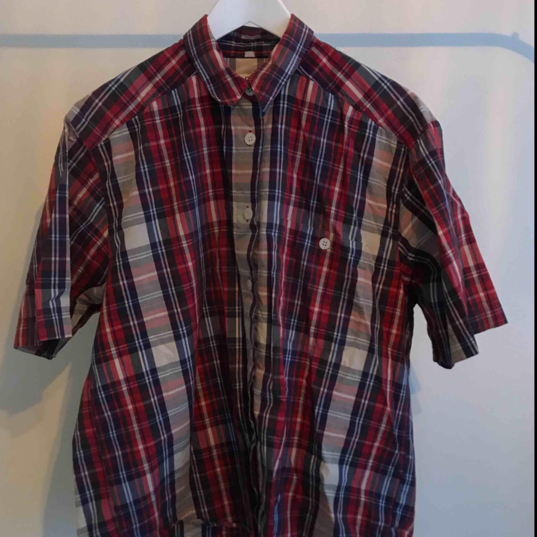 Rutig skjorta, uppskattad till L. 100% cotton. Använd en del men fortfarande i bra skick. Skrynklig nu då jag haft den knuten i midjan senast, vilket också blir snyggt! Frakt tillkommer. . Skjortor.