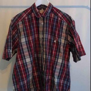 Rutig skjorta, uppskattad till L. 100% cotton. Använd en del men fortfarande i bra skick. Skrynklig nu då jag haft den knuten i midjan senast, vilket också blir snyggt! Frakt tillkommer.