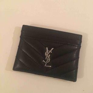 Finaste YSL korthållare (kopia) säljes! Får plats med 4 kort och så finns det en liten ficka för sedlar. Sparsamt använd! Fri frakt!