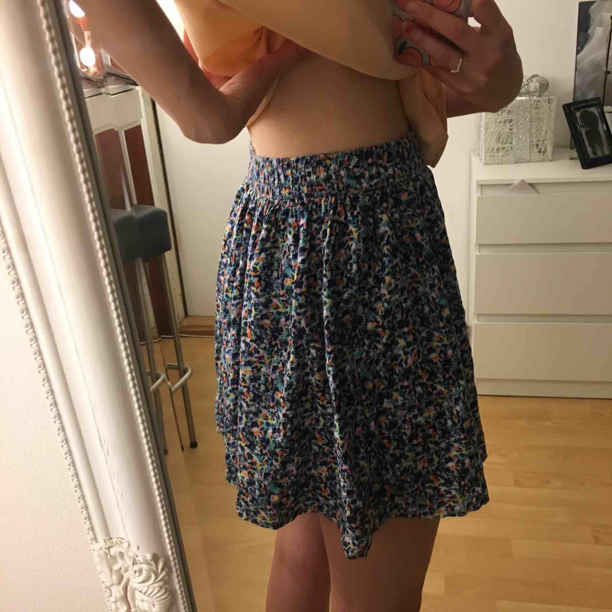 En oanvänd blommig kjol som lägger sig fint på kroppen 🌼. Kjolar.