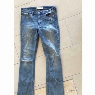 Bootcut Abercrombie & Fitch jeans med slitning på ena knät. Hög midja. Super sköna. Använd en gång. 4R = W 27 & L 33. Frakt ingår