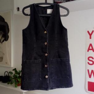 Svart/grå a-linje formad klänning i jeans. Använd 1 gång. Kort och tajt i passformen.