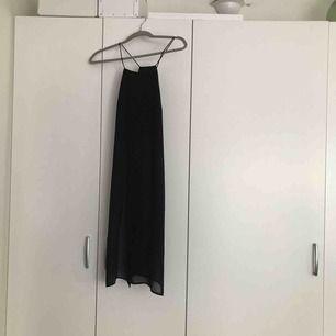 Ett långt linne/klänning med slits på sidorna. Täckande över bröst å mage men blir sedan transparant. Väldigt snygg över kjol eller byxor! I priset ingår frakt!