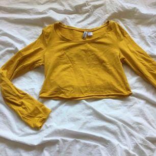 En avklippta långärmad senapsgul tröja! Den är jättefin och gör en outfit roligare!