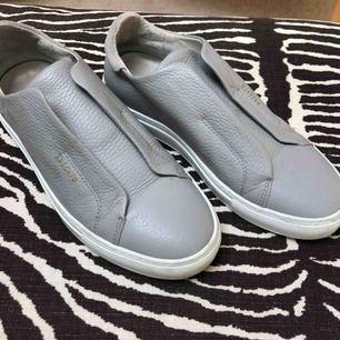 Sneakers från Axel Arigato, i grått läder med vid sula. Passar perfekt till våren!! Köpta i fel storlek så använda endast 2 gånger:) Nypris 1600kr