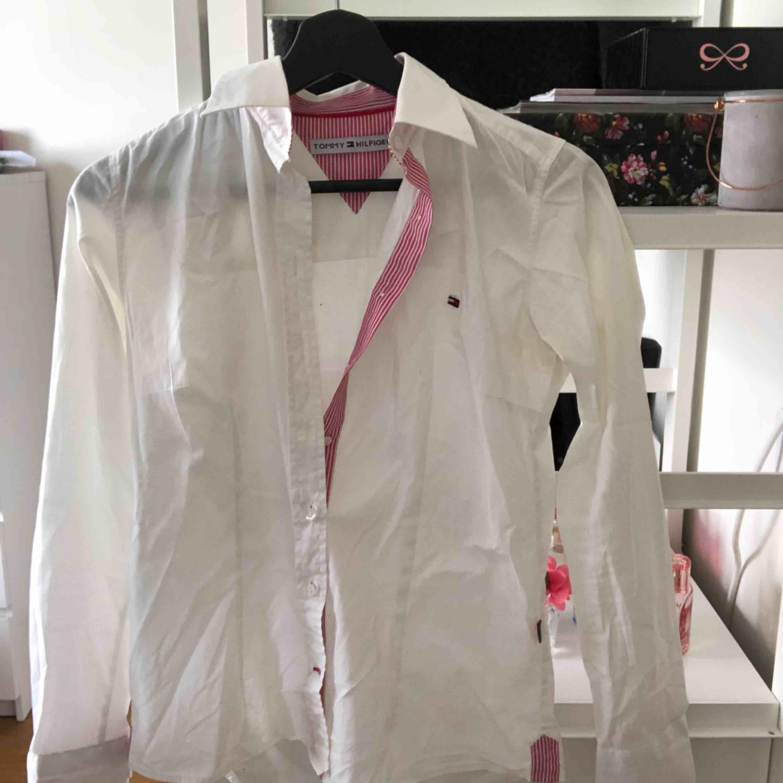 Snygg skjorta med rosa detaljer från Tommy Hilfiger, sitter rätt så tajt om kroppen men formar sig snyggt. Hyfsat gott skick, köparen står för frakt💖. Skjortor.
