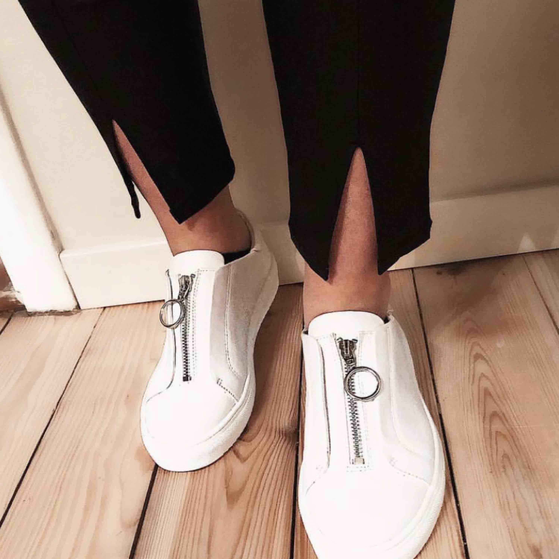 Vita sneakers med dragkedja från Nelly. Skor.