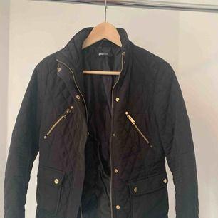 En svart jacka med gulddetaljer från Ginatricot. Aldrig använd! Köpt för några år sedan. Kan mötas upp i Stockholm annars plus frakt
