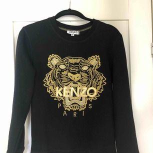 Svart långärmad tröja med guldigt Kenzo tryck. Aldrig använd! Tröjan är storlek M men väldigt liten i storleken. Hör av er för frågor!