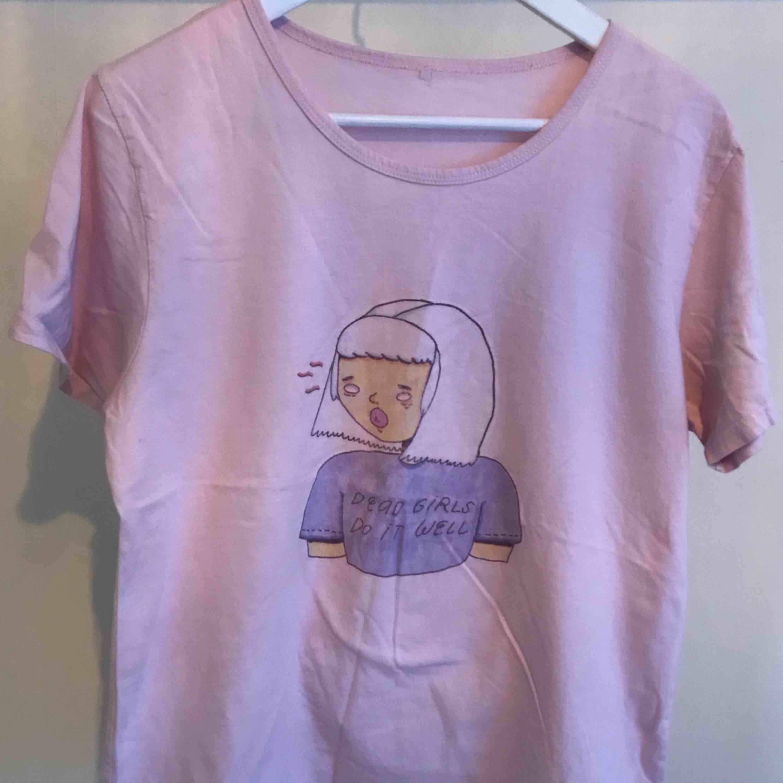 Ljusrosa t-shirt med tryck. Omärkt, men uppskattas till M/L. Använd en del men i gott skick! Frakt tillkommer. . T-shirts.