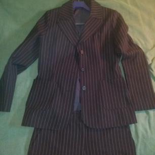 Svart kritsträcksrandig kostym, två delar. Oanvänd! Vida ben och hög i midjan.