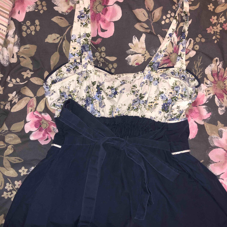 Söt 50-tals klänning i marinblå med fina blommor på överdelen. Knytning bak så man in reglera midjan, jättefin med underkjol! Köpt secondhand, står M som strl men passar XS/S. Klänningar.