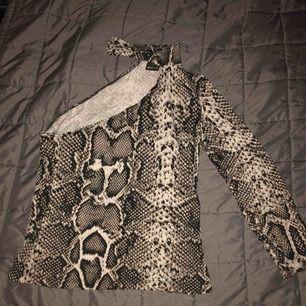 Väldigt snygg orm detaljerad bar axel tröja. (ONE SHOULDER.) Använd 1 gång. Ingen användning av plagget på grund av att den är för stor för mig.