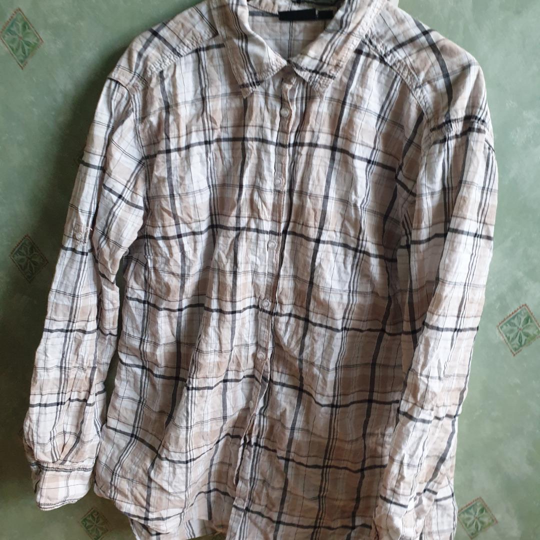 Variationer av beige och grått samlas på en skjorta som inte kommer till användning. Priset går att diskutera och frakt är inte inkluderat.. Skjortor.