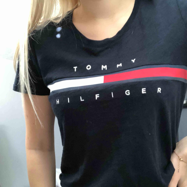 En marinblå Tommy hilfiger t-shirt, köpt i USA för ett år sedan, använd sparsam och ett fåtal gånger. Storlek XS men passar S.  Frakten är inräknad i priset.. T-shirts.