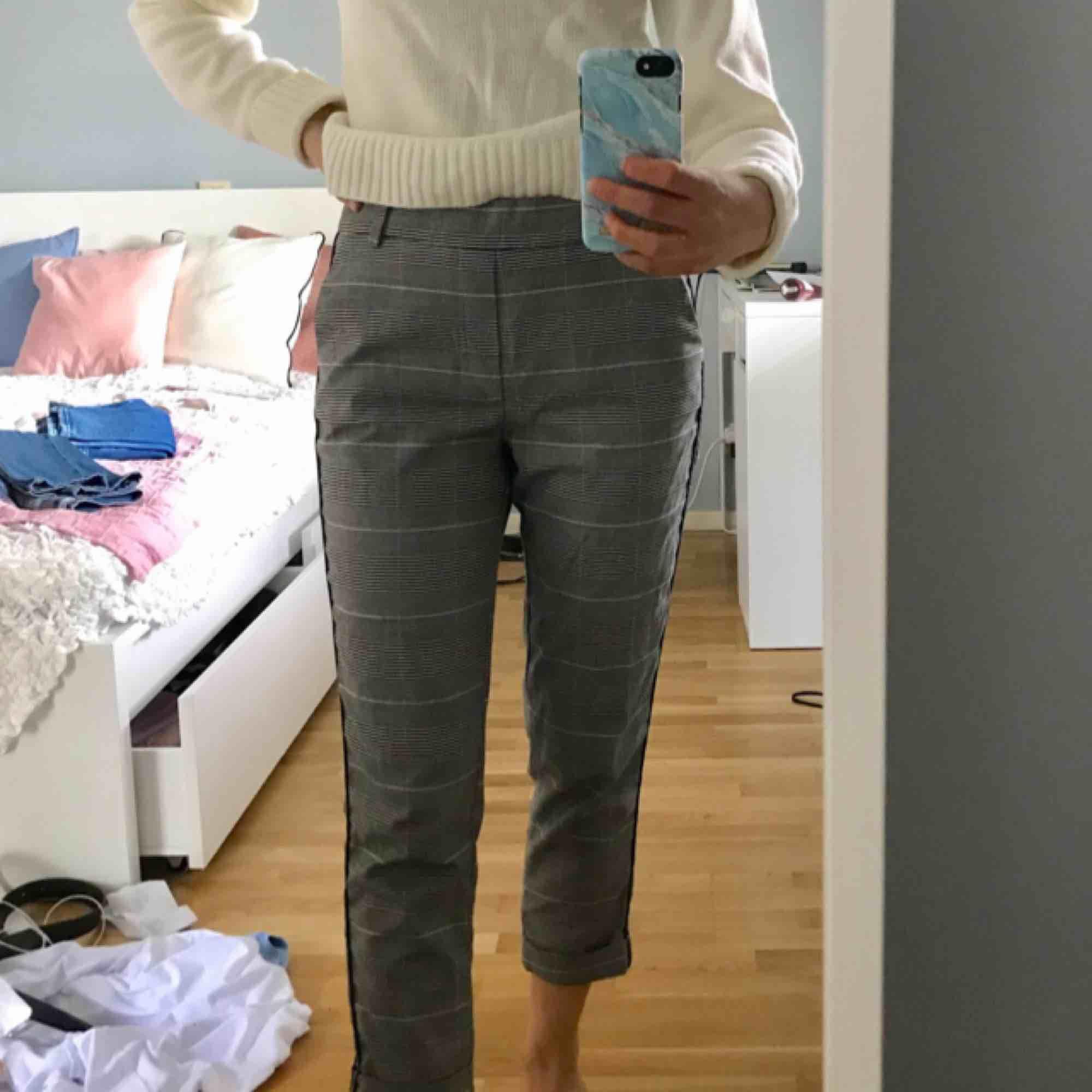 rutiga byxor från zara med en liten tint av ljusrosa i mönstret (syns kanske inte). två svarta streck på båda sidor av byxbenet. frakt tillkommer. Jeans & Byxor.