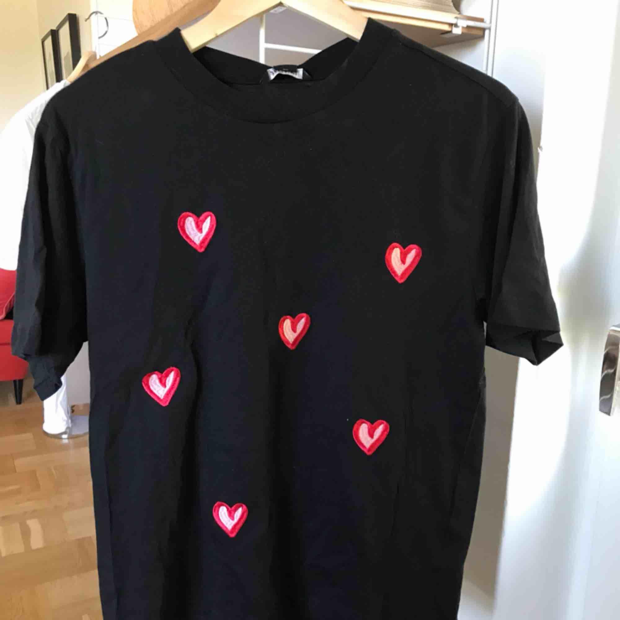 Helt oanvänd svart T-shirt från monki med broderade hjärtan. Prislapp kvar, storlek XS passar som S. T-shirts.