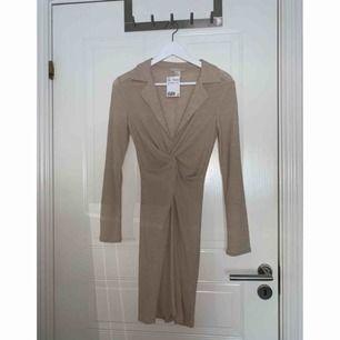 Beige långärmad klänning från H&M Trend, med djup V-ringning. Aldrig använd med lappen kvar. Originalpris 349 kr. Frakt ingår!