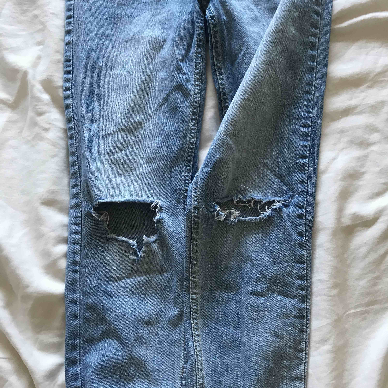 Ett par jeans från HM i ljusare tvätt med hål på bägge knäna. Frakt: 50kr. Jeans & Byxor.