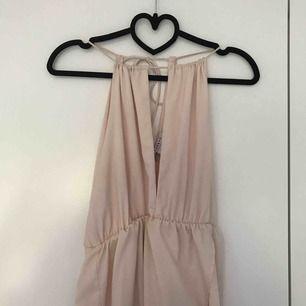 Rosa klänning med halter neck och öppen rygg samt framsida från Nelly trend. Frakt: 50kr