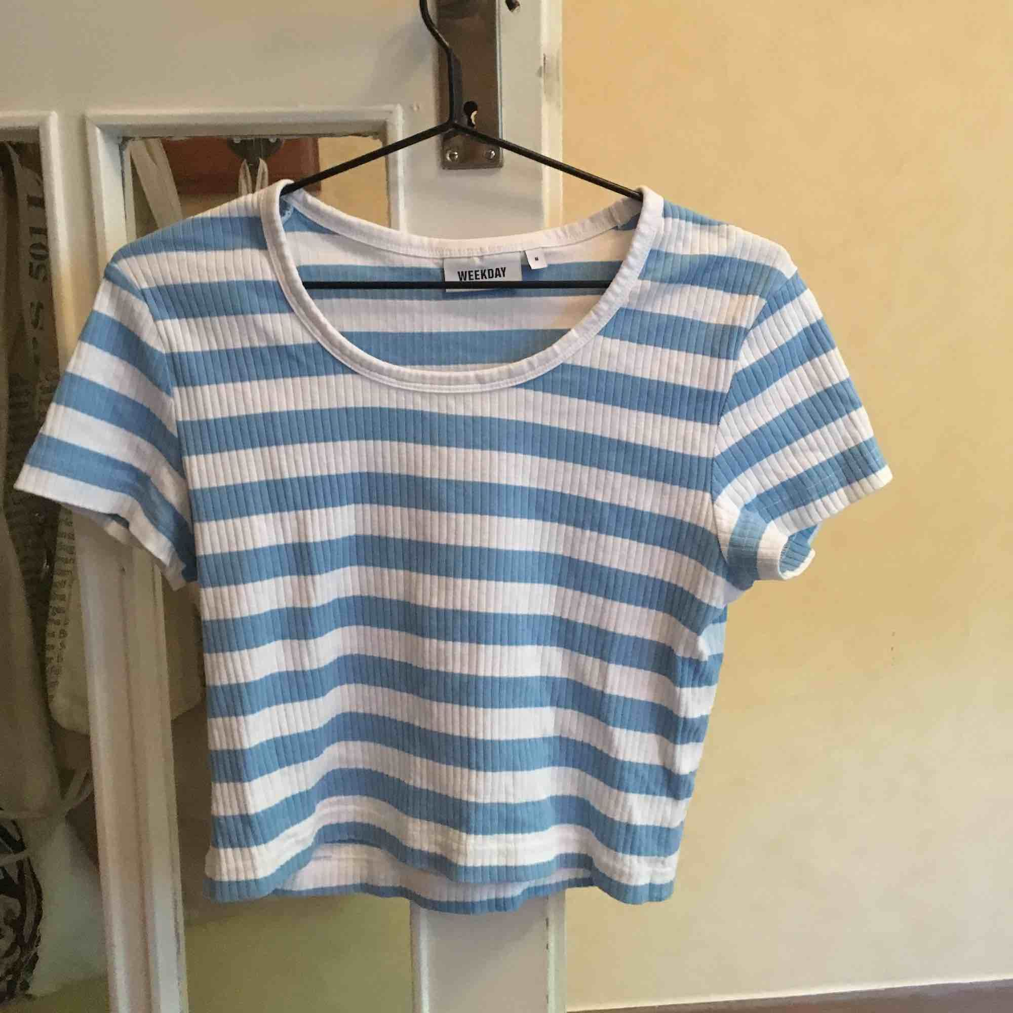 T-shirt från weekday köpt förra sommaren, mycket bra skick men använder inte längre!!  Den är cropped med lite tajt passform, superfin i sommar särskilt när kan blivit lite solbränd!  Kan mötas upp i Stockholm eller så stor köparen för frakt!. T-shirts.