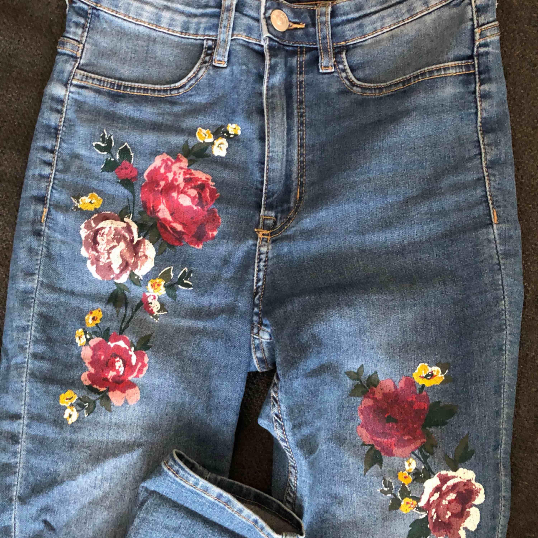 Högmidjade blåa jeans med fina blommor på! Väldigt sköna och framhäver fina former! Har använt de ett par gånger men de passar mig inte lika bra längre. FRAKT INGÅR I PRISET!. Jeans & Byxor.