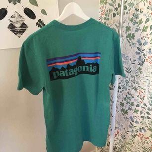 Oanvänd skitsnygg Patagonia T-shirt i turkos färg. Råkade beställa en för liten storlek, därför säljer jag nu(retur var så dyr😒) Nypris 350 kr. Möts upp i Stockholm eller fraktar🥰🦋🍃