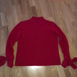 En röd stickadtröja köpt förra sommaren. Knappt använd. Fina knyt detaljer vid ärmarna. Köpare står för frakt :-)