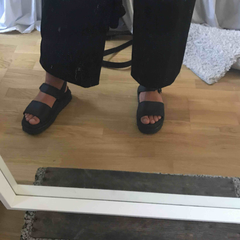 """Säljer dessa sjukt snygga och bekväma """"tofflorna"""" med lite tjockare sula ifrån dr.martens, väldigt bra skick då dem endast är använda några gånger under en sommar. Storlek 39 men passar mellan 38-40 då dem går att spänna in och ut. Skor."""