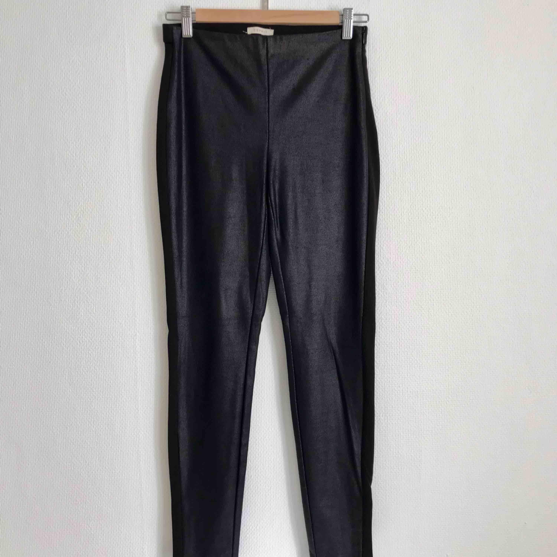 Tights i konstläder med revär. Svarta med en mörkblå ton. Perfekt skick och enbart använda en gång.. Jeans & Byxor.