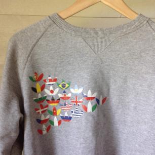 Grå Adidas sweatshirt med flaggor. Storlek small.