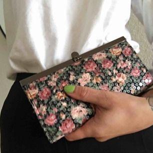 Plånbok i clutchmodell. Blommigt motiv med transparenta paljetter. Inköpt i amsterdam 🌷  Nyskick.