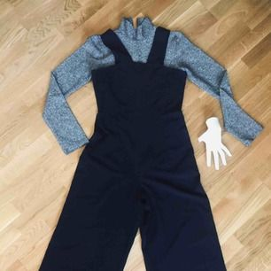 Svart Jumpsuit med tight midja & vida ben, & med blixtlås baktill.  Använd endast ett par gånger.  Mått midja 37cm (rakt över) Längd (axel till benslut) 139cm