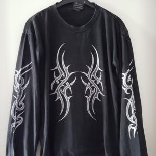 Vintage svart tröja med coolt tryck. Har ett litet igensytt hål baktill uppe vid ena axeln (se bild 2). Kan skickas om köparen står för fraktkostnaden.