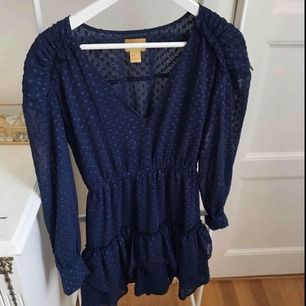 Fin marinblå klänning i skirt material med prickar, volanger nedtill. Använd 1 gång. Från H&M i storlek XS. För fler bilder, kontakta mig!