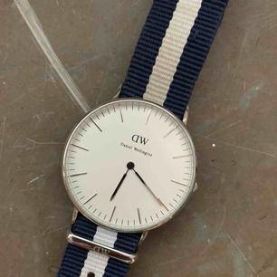 Daniel Wellington klocka i fint skick. Silverfärgad. Armbandet har viss tecken på användning (se bilder), annars i väldigt gott skick. Armbandet går att byta ut också om man vill det!
