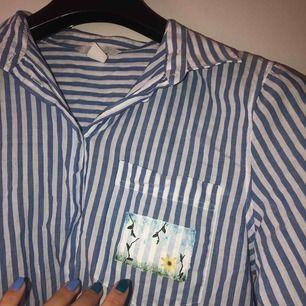 Superfin randig skjorta med egenmålat tryck. Mycket bra skick, kommer nytvättad och passar perfekt till blåa jeans! Skriv om du undrar något! Hämtas upp hemma hos mig eller postas mot fraktkostnad,50kr 🌼🌼🌼