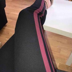 Kostymbyxor med detaljer på utsida ben, i form av två linjer i vinröd färg.  Byxorna är supersköna och nästintill helt oanvända, dom kommer ifrån Lindex Storlek; 38