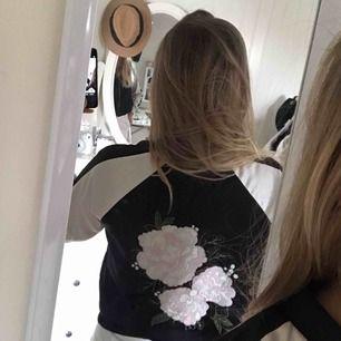 Svart vit tröja med dragkedja som öppning, samt ett blommigt broderat tryck på baksidan Ifrån Gina Tricot