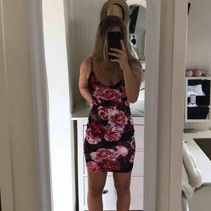 En mörkblå klänning med rosa/röda blommor, använd 1 gång, den är mycket stretching och sitter skönt och lätt