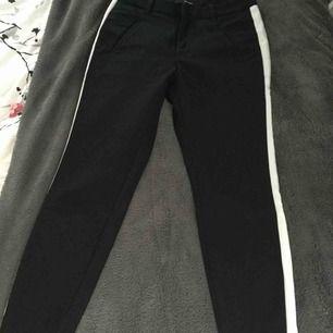 Svarta kostymbyxor med en hit rand på sidan, små i storleken Köparen står för frakten