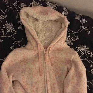 Ljusrosa leopardmönstrad jumpsuit i 100%polyester, jätte mjuk och skön o ha på sig om man fryser. Sparsamt använd så den är helt felfri. Frakt tillkommer