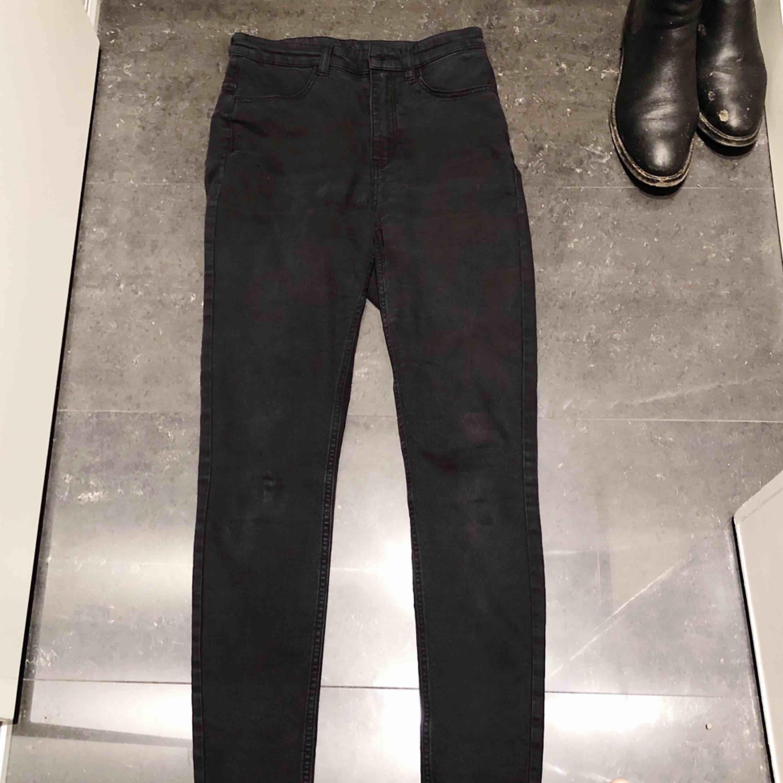 Vanliga svarta high waisted jeans från H&M i storlek 36. Säljer billigt för om ingen köper kommer de att gå till återvinningen. Vet inte varför det ser ut som att det är fläckar på knäna i bilden men kan skicka bilder som bevis att de är helt rena.. Jeans & Byxor.