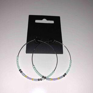 Silvriga hoops örhängen med pärlor i fina färger, köpta på Åhléns för 299kr, från märket Pilgrim. Aldrig använda! 100kr inklusive frakt. Ca 4cm diameter
