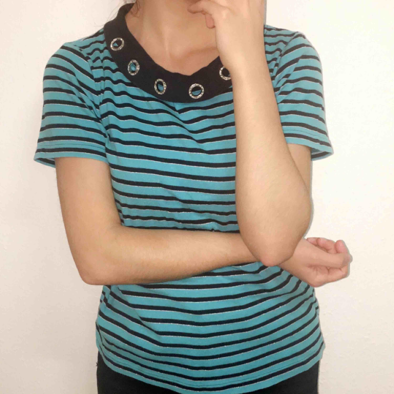 En randig T-shirt med diameter runt halsen och glittriga vita streckar. Säljs till ett billigt pris. T-shirts.