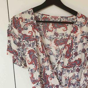 Mönstrad wrap-klänning från Indiska strl L. Band i midjan + ett på insidan för att knyta ihop klänningen. Köpt förra året, tyvärr bara använd 2 ggr pga för liten. Perfekt sommarklänning!