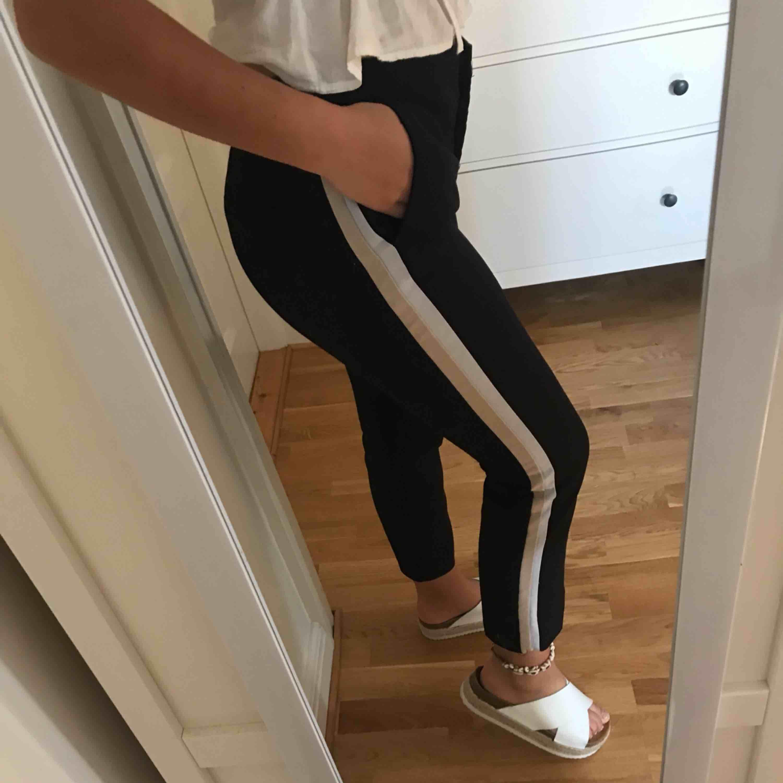 Ett par svarta kostymbyxor med beige/vita ränder på sidan av benen, dom är ifrån Zara och är använda 1 gång. Mycket bekväma och är egentligen helt nya. Jeans & Byxor.