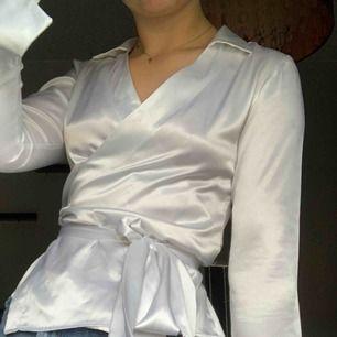 Helt underbar vit satin blus med omlottknytning från Paris! Köpt second-hand. 150 kr inkl frakt 💓